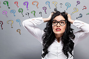 IRS form 990 questions answered. Woman in glasses pulling at her hair, question marks surround her.